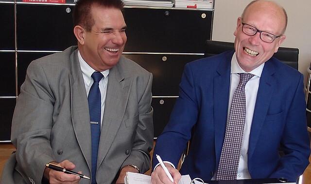 Udo Schmidt, Geschäftsführender Direktor der Immanuel Diakonie (rechts) und Generalübernehmer Hans J. Benner unterzeichnen den Generalübernehmervertrag.