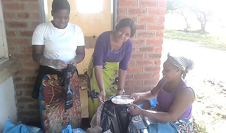 Noela and two songani volunteers with soya pieces and flour